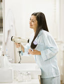 Hispanic woman blow drying hair — Stock Photo