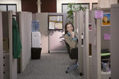 Hispanic businesswoman looking out from cubicle — Stock Photo