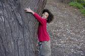 Africa boy hugging tree — Stock Photo