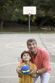 Hispanic father and son on basketball court — Stock Photo