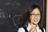Asian female student in front of blackboard — Stock Photo