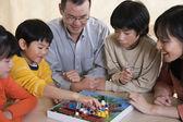 Família asiática, jogando o jogo de tabuleiro — Foto Stock
