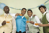 Multi-ethnic men in suits holding cups of punch — Stock Photo