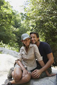 Hispanic couple hugging on rocks — Stock Photo