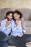 African twin sisters eating apples — Stock Photo