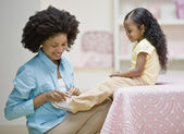 African mother tying daughter's shoe — Stock Photo