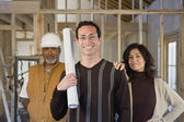 Hispanic couple and construction worker at new construction site — Stock Photo