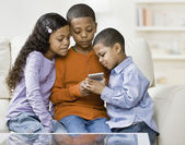 Mixed Race siblings looking at hand-held game — Stock Photo