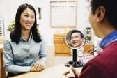 Asian optician assisting customer — Stock Photo