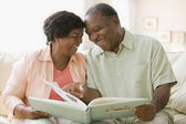Senior African couple looking at photo album — Stock Photo