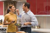 Multi-ethnic couple tasting food — Stock Photo