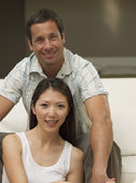 Multi-ethnic couple sitting on sofa — Stock Photo