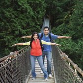 Indian couple wearing backpacks on footbridge — Stock Photo