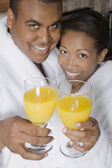 African couple toasting with orange juice — Stock Photo