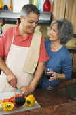 Woman smiling at husband chopping vegetables — Stock Photo