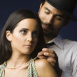 Hispanic man fastening wife's necklace — Stok fotoğraf