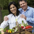Hispanic couple with basket of vegetables — Stock Photo #23322228