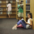 Multi-ethnic students reading library books — Stockfoto