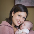 Hispanic mother hugging baby — Stock Photo