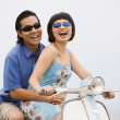 Asian couple sitting on motor scooter — Stock Photo
