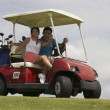 Hispanic couple driving golf cart — Stock Photo