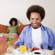 African man carrying breakfast in bed tray — Stock Photo