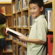Asian boy holding library book — Stock Photo