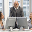 Multi-ethnic businesspeople behind computers — Stock Photo