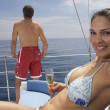 Multi-ethnic couple on sailboat — Stockfoto