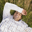 Pacific Islander man laying in field — Stock Photo