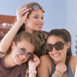 Multi-ethnic teenaged girls trying on sunglasses — Stock Photo