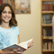 Girl holding library book — Foto Stock