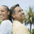 Multi-ethnic couple standing back to back — Stock Photo