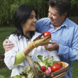 Hispanic couple with basket of vegetables — Stock Photo