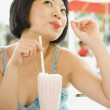 Asian woman drinking milkshake — Stock Photo