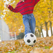 Hispanic boy kicking soccer ball — Stock Photo