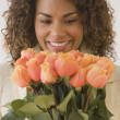 African woman holding bouquet of flowers — Stock Photo