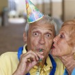 Senior woman kissing husband on birthday — Stock Photo #23323578