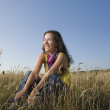 Stock Photo: Hispanic womsitting in field