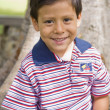 Hispanic boy in front of tree — Stock Photo
