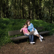 Hispanic mother and daughter looking at laptop in woods — Stock Photo #23323704