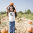 Hispanic girl holding pumpkin on head — Stock Photo