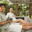 Asian couple on patio with coffee — Stock Photo