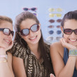 Stock Photo: Multi-ethnic teenaged girls trying on sunglasses