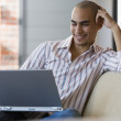 Stock Photo: AfricAmericmlooking at laptop