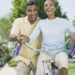 Mixed Race woman riding girl's bicycle — Stock Photo