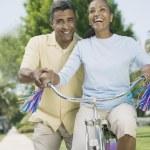 Mixed Race woman riding girl's bicycle — Stock Photo