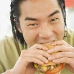 Asian man eating hamburger — Stock Photo