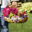 Hispanic woman holding basket of flowers — Stock Photo