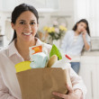 Hispanic woman holding grocery bag — Stockfoto